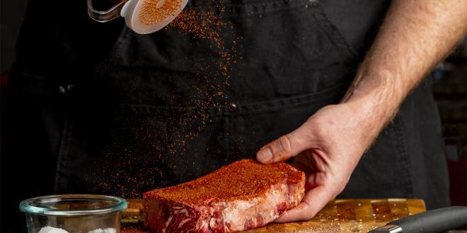 a man sprinkling dry rub on a strip steak